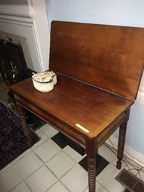 This is an antique  cherry spool leg game table.