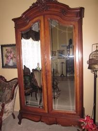 Wood carved mirrored door armoire with cabriolet legs.