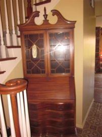 Wood secretary desk with four graduating drawers.