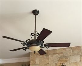 Ceiling fan located in the living room is ornate and very nice.