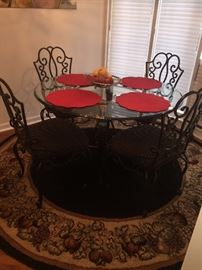 GORGEOUS BLACK WROUGHT IRON AND GLASS TOP TABLE WITH 4 UPHOLSTERED CHAIRS