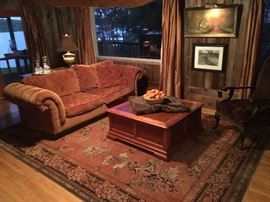 Comfortable upholdstered sofa by Paladin Industries, a vintage Oriental style rug, contemporary coffee table and faux mink fur seat arm chair