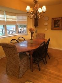 Antique Drop Leaf Dining Table with two upholstered side chairs and black Windsor chairs