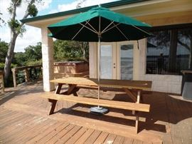 Long picnic table with attached benches and umbrella