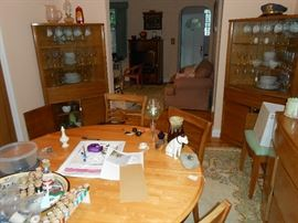 Blonde corner cabinets, buffet, chairs, china, stemware, oil lamp, platters, cake plates, wooden spools, Ethan Allen EC, more.