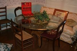 Large glass top table on Rattan base, Brass & Wood Dessert cutlery set, 2 primitive chairs, w carved/needlepoint chairs