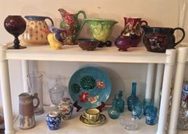 """France P.V."" purple glass vase, French ceramic polka dot pitcher, Frie Onnaing majolica pitcher (also French), German bird pitcher, Chinese cloisonne bowl, interesting yellow & green vase, Czech majolica pitcher, small pink iridescent vase, Decoro pitcher (England). Bottom row: Pink Wedgwood Jasperware pitcher, ginger jars, turquoise majolica plate, Quimper cup & saucer, blue glass bottles, decorated blue glass decanter & tumblers."