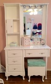 White vanity dressing table has overhead glamour lights, light switch, mirror, and a storage ottoman with cushioned seat.