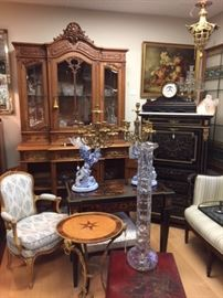 A tall hand-carved French cabinet full of American Brilliant Period cut crystal as well as some European crystal, a pair of Gallé delftware lion candelabra, a 19th century French ebonized secrétaire à abbatante, a very tall blown-glass vase, a red lacquered coffee table, and more.