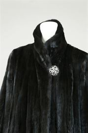 View of the black gamma coat with antique button