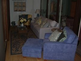 Nice comfortable chairs and soffa with faux wicker table and area rug.