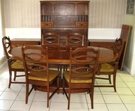Oval Dining Room Table on Dual Column Base w/leaf shown on the right wall.  There are  4 Side and 2 Arm Chairs.  Pictured in the background is an open Hutch and 2 Lowboy 3-Drawer Chest.  All sold separately.