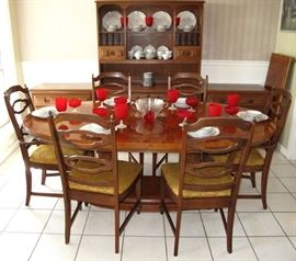 Oval Dining Room Table on Dual Column Base w/leaf shown on the right wall. Set with Bavarian China & Red Stemware  There are  4 Side and 2 Arm Chairs.  Pictured in the background is an open Hutch and 2 Lowboy 3-Drawer Chest.  All sold separately.