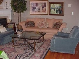 Fine uphostered sofa and chairs; room-sized Oriental rug; glass and brass coffee table