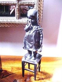 Bronze of a girl standing on a stool