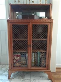 This is a cool piece. It's a small bookcase, with mirror at top and wire mesh to keep the help outta the liquor.