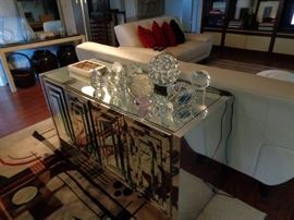 MIRRORED SIDEBOARD WITH LOTS OF PAPERWEIGHTS ON THE TOP OF IT.