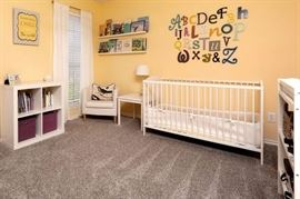 Baby nursery. Convertible crib. 2 changing tables. small tables and storage.  Table, chair & lamp. Unique wall decor