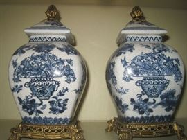 Pair of blue and white lidded urns on brass bases