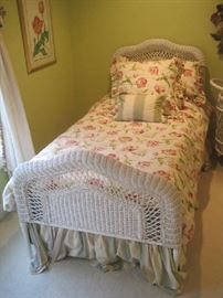 One of a pair of white wicker twin beds with bedding