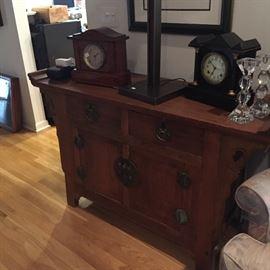 Asian cabinet, 2 drawers, 2 doors, metal mounts; 2 antique mantel clocks, pair of modernist glass candlesticks.