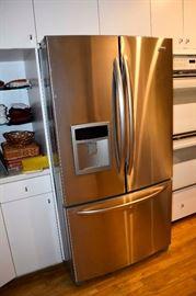 Kenmore stainless steel double door refrigerator with freezer door at bottom.