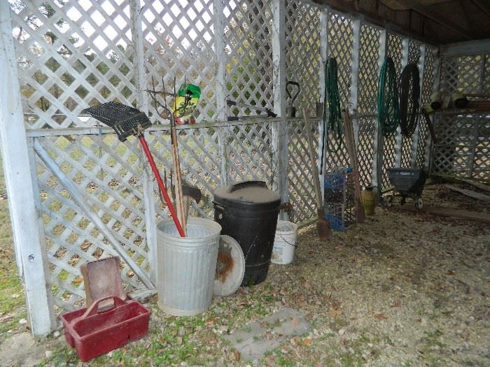 Old tool box, galvanized and plastic trash cans, shovel, rake, etc.