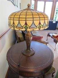 LEADED SLAG GLASS LAMP SHADE WITH PERIOD BASE.  ROUND DUNCAN PHYFE LEATHER TOP LAMP TABLE