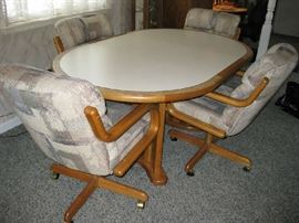 oval table and 4 padded rolling chairs
