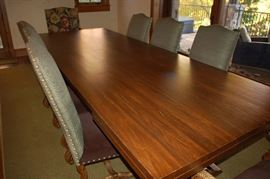 Large mahogany custom dining table with covered high back chairs.  Table is 10' x 4'