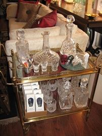 Heavy brass and glass bar cart, crystal and glass decanters.