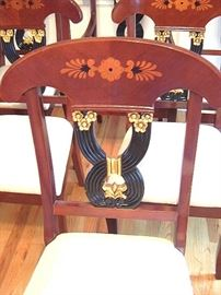 Close up of wood inlay, & gilt & black center back rest on set of dining room chairs.