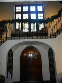 Foyer:  This is an interior view of the double-arch front door where you will enter.  The windows shown above face the front of the house.  The greenery continues up the iron railings and around to the loft area.... keep going.