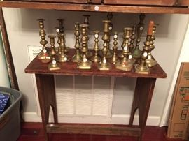 Antique brass candle sticks on a small primitive table