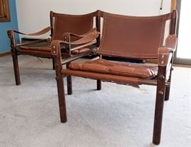 A pair of Arne Norell Safari chairs with slung leather arms and a rosewood frame.