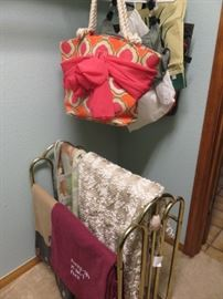 Brass quilt rack and vintage handbags.
