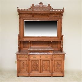 An American Eastlake walnut mirrored sideboard. Features a large and ornate style with a carved pediment featuring turned finials to the sides and elaborate pieced ladder like detailing and carved scalloped and foliate detailing. The top also features incised repeated geometric designs and carved geometric designs in relief throughout. The large beveled mirror rests over a lower shelf for additional display storage. The shelf is finished with a scalloped edge and pierced and incised detailing with carved finials to the sides. There is handsome burl walnut veneer noted throughout the piece. The sideboard features three shelves of tapered edge rose marble to the top of the lower cabinet. The lower cabinet features three drawers for storage and three lower cabinets. The drawers are each finished with brass bails and pulls and the drawers and doors each features brass escutcheons. The two side cabinet doors features incised floral detailing to the burl front doors and the two central cabin