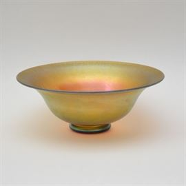 A signed F. Carder Steuben Aurene art glass bowl. Features a gold tone finish with slight round foot. The piece, in a lustrous golden iridescence is marked aurene and signed F. Carder to the bottom. The piece features a slightly rolled lip, over the tapered body, rough pontil on the base, hand engraved marks, the color is radiant, picking up greens, blues and reds in the spectrum.