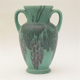 A 1928 Rookwood vellum amphora vase. Features a matte finish with an aqua tone under glaze and a violet and navy abstract floral design throughout. The piece is stamped with the Rookwood Pottery mark with XXVIII and 2783 below. There is some writing in red to the bottom, but the piece is unsigned.