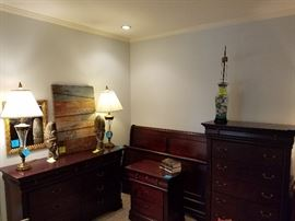 Queen bedroom suite which includes sleigh bed, upright dresser, nightstand, and triple dresser with mirror.