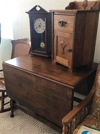 Antique gate leg table with two extensions.  Small oak nightstand/side table.  Chiming clock with pendulum.  Cane rocking chair.