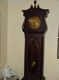 Tall case clock with brass pendulum