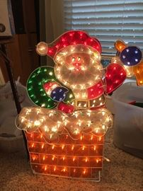 Santa is ready to come down  the chimney in this light-up decoration.