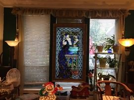 View of Main Room with Tiffany window in center flanked by two art nouveau floor lamps with beautiful glass globes and bronze like columns. Santa Xmas decoration lights up! Metal and glass etagere holding plants.