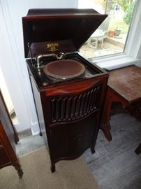 """""""Sonora"""" Vintage Record Player. Beautiful dark wood Cabinet with Locking Double Doors to bottom portion of the cabinet. Located in the bottom are many vintage long play albums. Crank handle is located on the right side of the cabinet."""