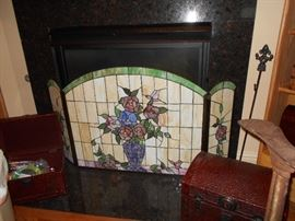 The stained glass fireplace screen is intricate!