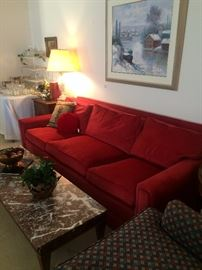 Three-cushioned red sofa; long marble-top coffee table