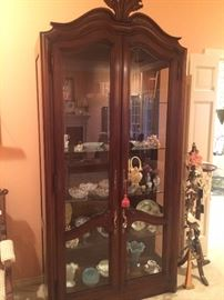"""Tall display cabinet with glass front and sides and filled with """"pretties"""""""