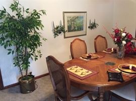 Beautiful Thomasville dining table with 6 matching chairs, pads, and 2 leaves.  artificial plant, wall decor and picture.