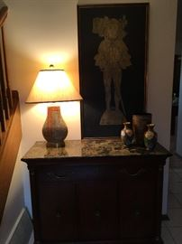 Chest with marble top with silverware drawer, stone lamp, cloisonné vases, print of rubbing.
